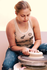 Jessica creates a vessel on a potter's wheel using a process called throwing.